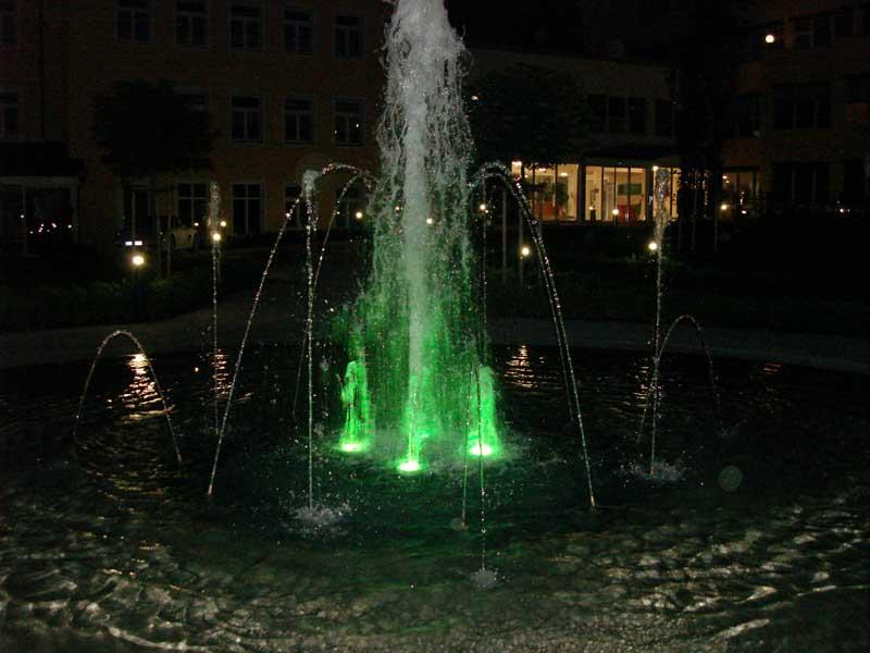 Grün beleuchteter Springbrunnen in der Nacht