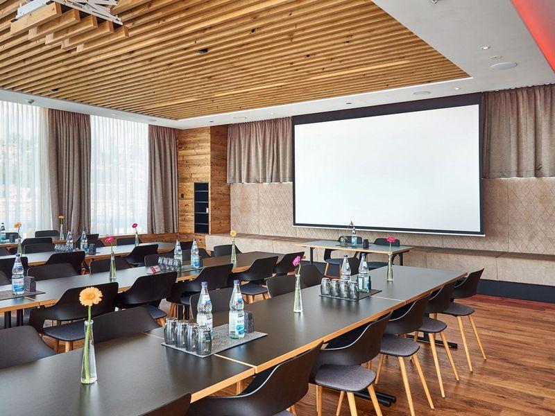 Moderner Tagungsraum mit Leinwand und heller Beleuchtung