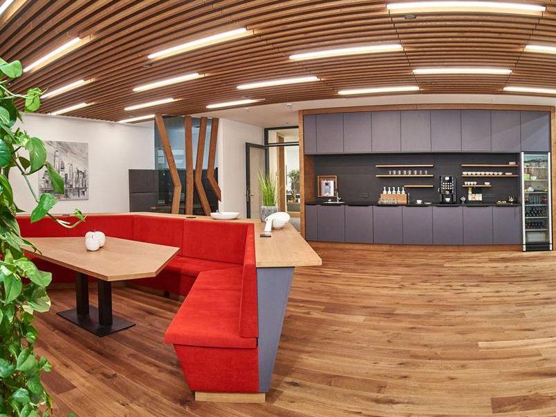 Wartebereich der Firma Erl mit Sitzmöglichkeiten und Bar